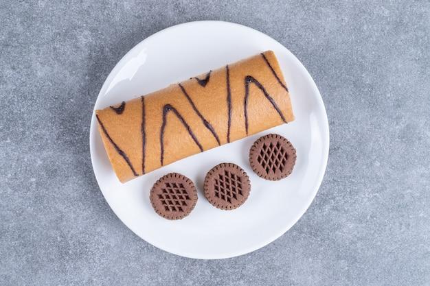 Pyszna słodka bułka i ciastka na białym talerzu