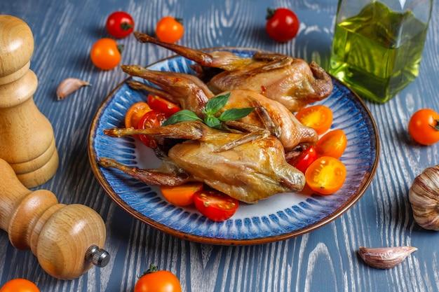 Pyszna smażona przepiórka z ziołami i pomidorkami koktajlowymi.