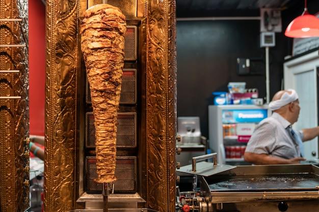Pyszna smażona shawarma na rożnie w środku w restauracji fast food w tle