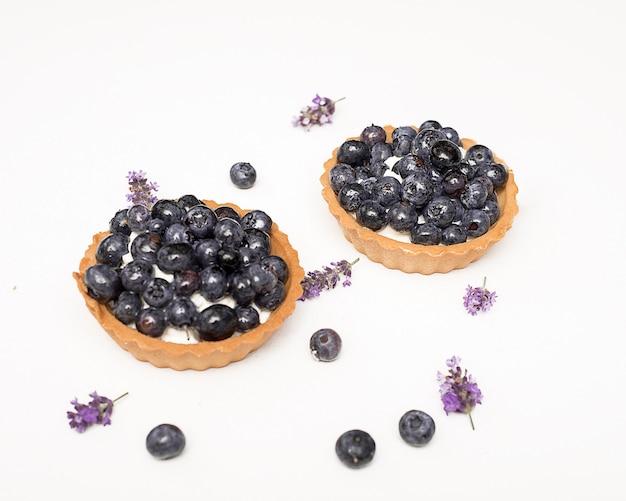 Pyszna, świeża deserowa tartaletka z kruchego ciasta ozdobiona jagodami wśród jagód i kwiatów lawendy. koncepcja pieczenia piekarni, słodyczy. close-up zdjęcie, odizolowane, kopia przestrzeń.