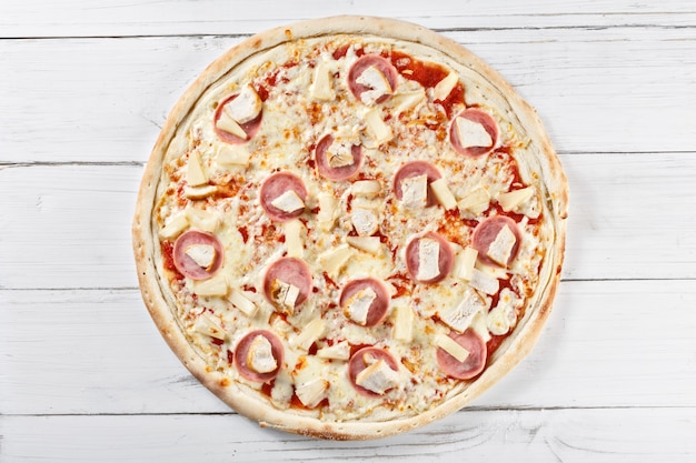 Pyszna świeża pizza chikita z kurczakiem i ananasem podawana na drewnianym stole