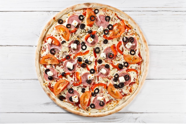 Pyszna świeża pizza serwowana na drewnianym stole. widok z góry.