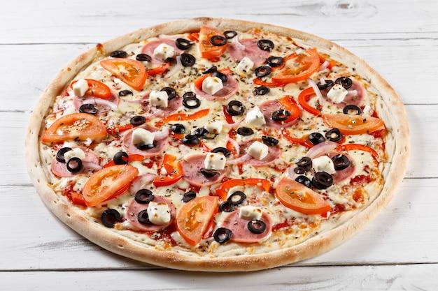 Pyszna świeża pizza serwowana na drewnianym stole