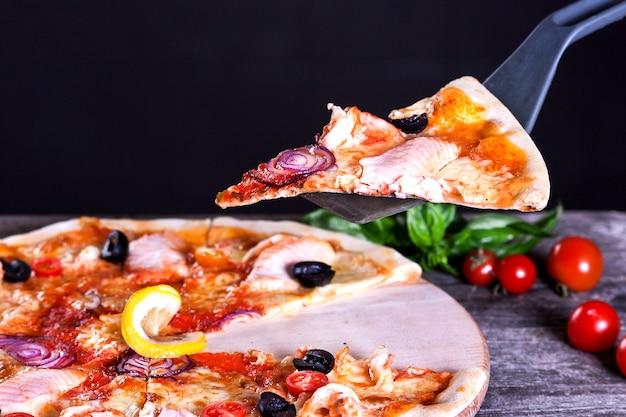 Pyszna świeża pizza z czerwoną rybą i mozzarellą na drewnianym tle. widok z góry.
