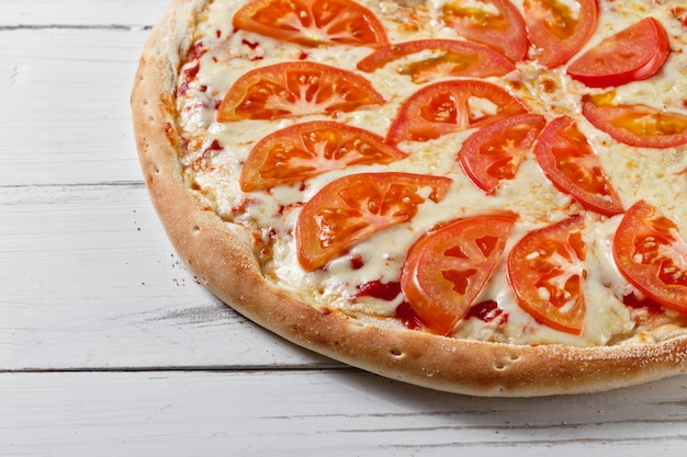 Pyszna świeża pizza z pomidorami i serem podawana na drewnianym stole