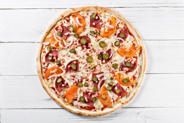 Pyszna świeża pizza z szynką i korniszonem podawana na drewnianym stole