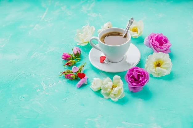 Pyszna, świeża poranna kawa espresso z piękną gęstą pianką na lazurowej ścianie stołu z mglistymi bąbelkami pąki róży, leżał płasko. filiżanka kawy, kwiaty róż.