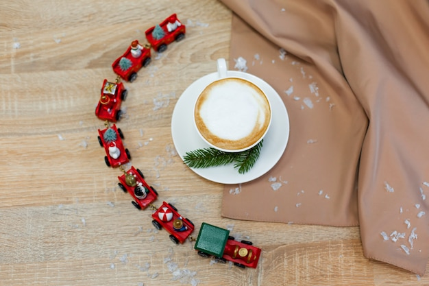 Pyszna, świeża świąteczna poranna kawa cappuccino w ceramicznej białej filiżance na drewnianym stole z ozdobnymi świątecznymi pociągami, czerwonymi ozdobami, świetlikami i świerkowymi gałęziami.
