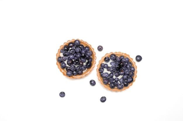 Pyszna, świeżo deserowa tartaletka z kruchego ciasta ozdobiona świeżymi jagodami wśród jagód. koncepcja pieczenia piekarni, słodyczy. close-up zdjęcie, odizolowane, kopia przestrzeń. widok z góry