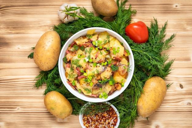 Pyszna tartiflette z ziołami i warzywami na drewnianym stole. widok z góry.