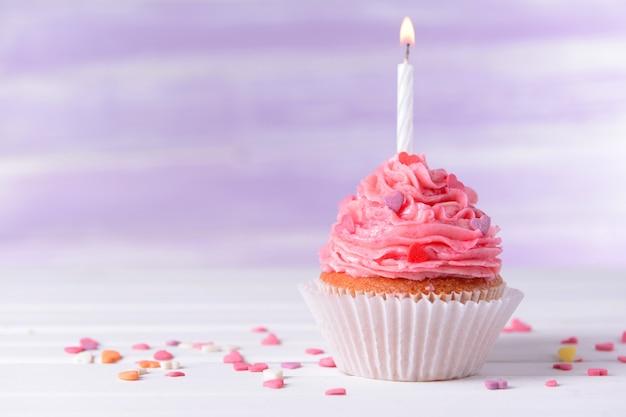 Pyszna urodzinowa babeczka na stole na jasnofioletowym