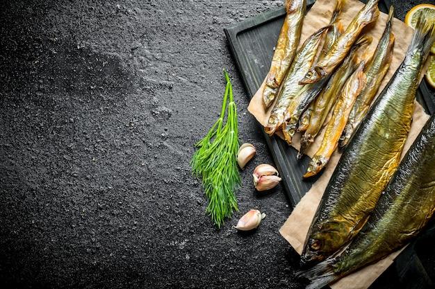 Pyszna wędzona ryba z koperkiem i ząbkami czosnku. na czarnym rustykalnym