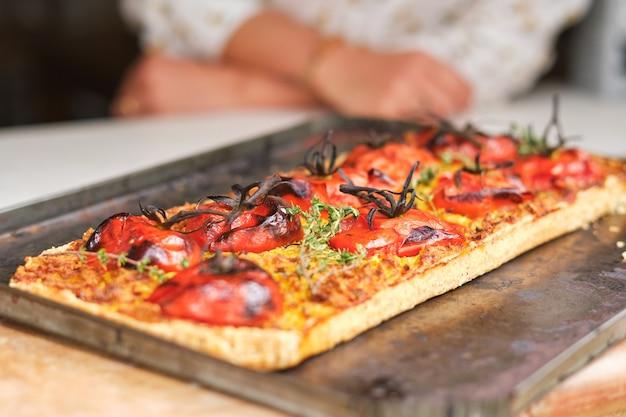 Pyszna wegańska pizza na patelni do pieczenia przeciwko osobie uprawnej