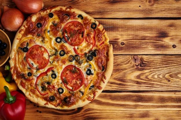 Pyszna wegetariańska pizza z oliwkami, papryką i pomidorem na drewnie. rustykalny. jedzenie. skopiuj miejsce