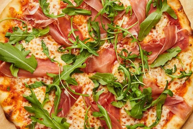 Pyszna włoska pizza z szynką parmeńską i rukolą, ser mozzarella