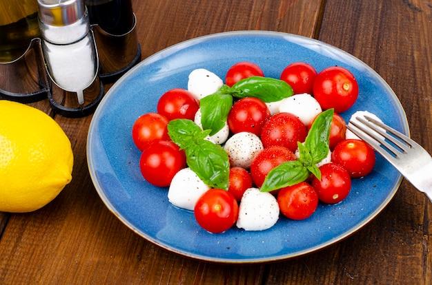 Pyszna włoska sałatka caprese z bazylią, mozzarellą i pomidorkami koktajlowymi. zdjęcie studyjne.