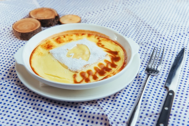 Pyszna zapiekanka z sera w ceramicznym garnku.