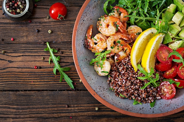 Pyszna zdrowa miska buddy z krewetkami, pomidorem, awokado, komosą ryżową, cytryną i rukolą na drewnianym stole. zdrowe jedzenie. widok z góry. leżał płasko.
