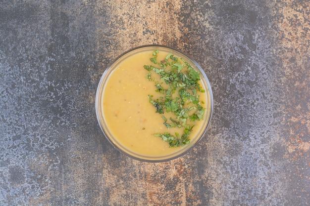 Pyszna żółta zupa z zieleniną na marmurowej powierzchni