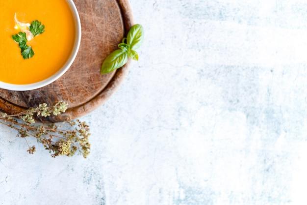 Pyszna zupa dyniowa w misce na marmurowym stole