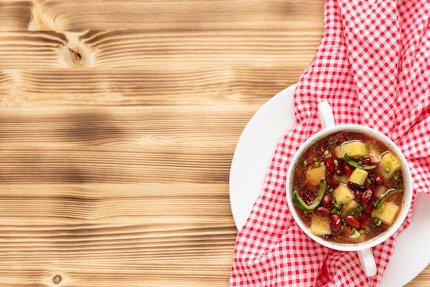 Pyszna zupa fasolowa z mięsem na drewnianym tle. skopiuj miejsce. widok z góry.