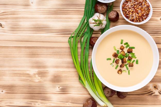 Pyszna zupa kasztanowa na drewnianej przestrzeni z przyprawami i cebulą. widok z góry. miejsce do skopiowania.