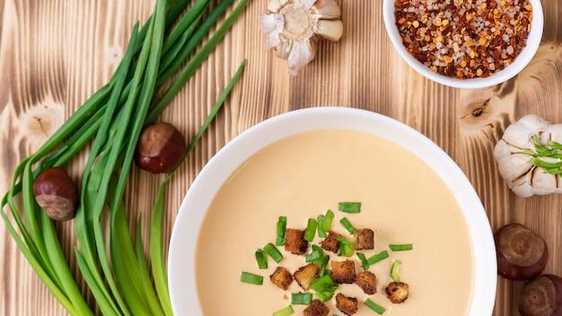 Pyszna zupa kasztanowa na drewnianym stole z przyprawami i cebulą. widok z góry.