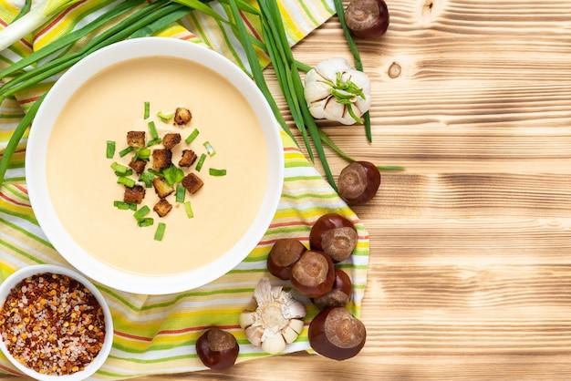 Pyszna zupa kasztanowa z grzankami i ziołami na drewnianym stole. widok z góry. skopiuj miejsce.