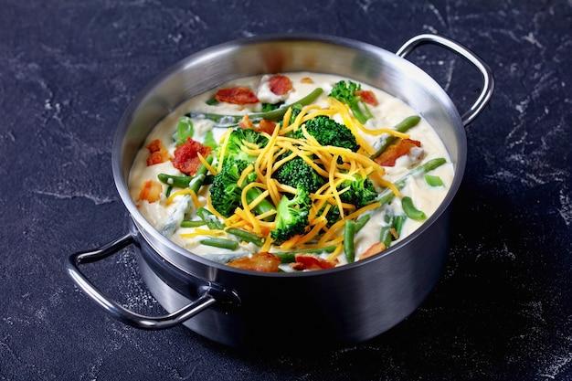Pyszna zupa krem z brokułami, fasolką szparagową, smażonym boczkiem i rozdrobnionym serem cheddar w metalowej zapiekance na betonowym stole, zbliżenie