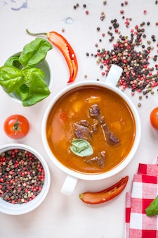 Pyszna zupa pomidorowa z mięsem na białym rustykalnym drewnianym stole ze świeżymi pomidorkami cherry, liśćmi bazylii, papryczką chili i ręcznikiem kuchennym w czerwoną kratkę. składniki na zupę. widok z góry