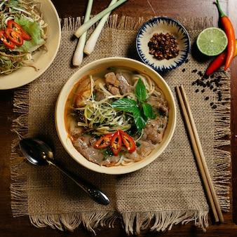 Pyszna zupa z mięsem i makaronem w białej misce