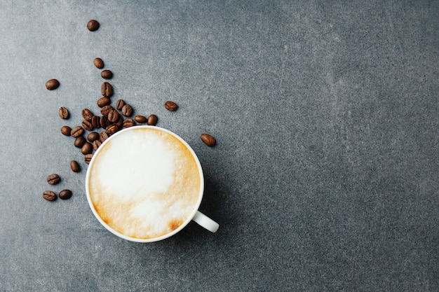 Pyszne apetyczne cappuccino w filiżance z fasolą na betonowym stole.