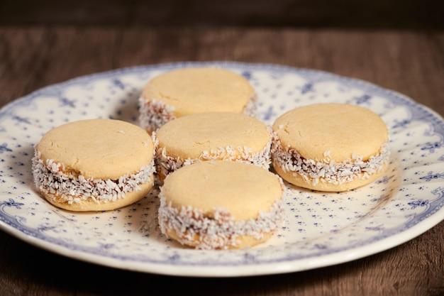 Pyszne argentyńskie ciasteczka alfajores cornflow z kremem dulce de leche z bliska na białym tle. białe makaroniki waniliowe na białym tle. francuski delikatny deser na śniadanie.