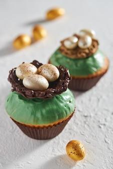 Pyszne babeczki udekorowane polewą z gniazdem i jajkami czekolady na stole