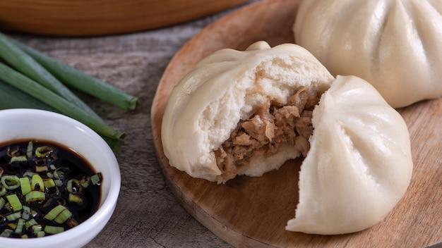 Pyszne baozi chińskie bułeczki gotowane na parze mięso jest gotowe do spożycia na talerzu służącym i parowiec z bliska kopia przestrzeń koncepcja projektowania produktu