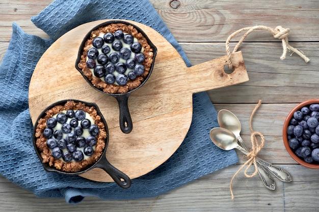 Pyszne borówki jagodowe z kremem waniliowym. tarty są na rustykalnej drewnianej desce na niebieskim ręczniku tekstylnym na drewnianych deskach.
