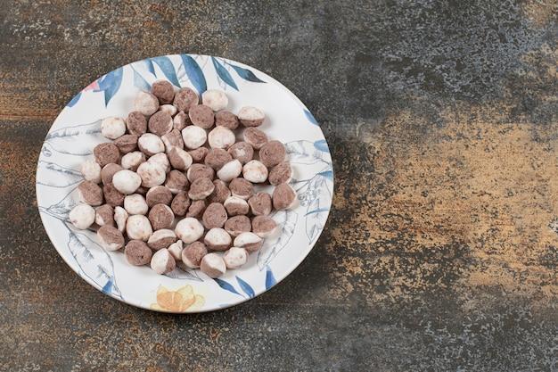 Pyszne brązowe cukierki na kolorowym talerzu.
