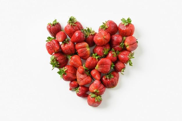 Pyszne brzydkie dojrzałe truskawki organiczne w kształcie serca na białym tle. widok z góry. koncepcja ekologicznych produktów ekologicznych.