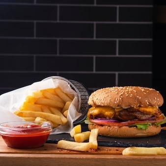 Pyszne burgerowe mięso fast food, cebula, ser i sałata ozdabiają frytki i keczup.