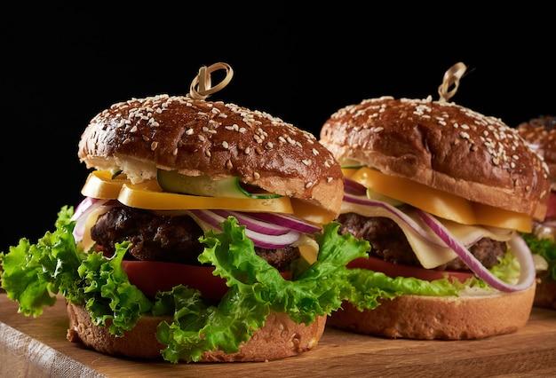 Pyszne burgery ze smażonym kotletem wołowym, pomidorem, sałatą i cebulą, chrupiącą białą mąką pszenną