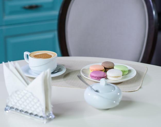 Pyszne cappuccino i makaroniki przygotowane na stole dla gościa