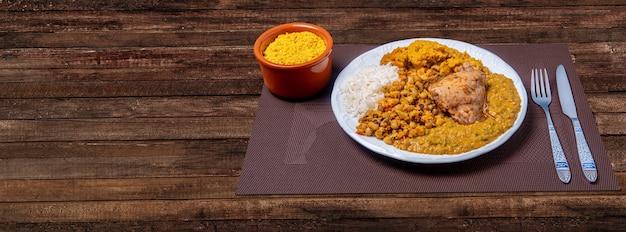 Pyszne caruru. tradycyjne danie afro-brazylijskie z okry i suszonych krewetek w towarzystwie vatapy, fasoli, ryżu, kurczaka i farofy. na drewnianym stole.