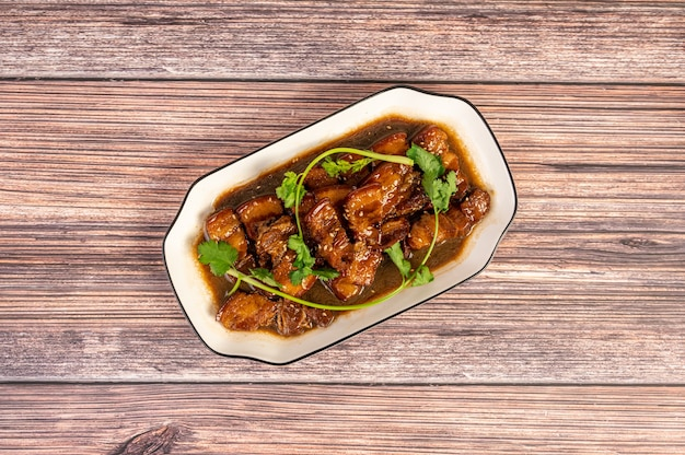 Pyszne chińskie duszone mięso na talerzu leży na drewnianym stole