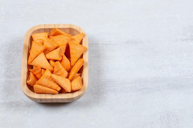 Pyszne chrupiące krakersy na drewnianym talerzu.