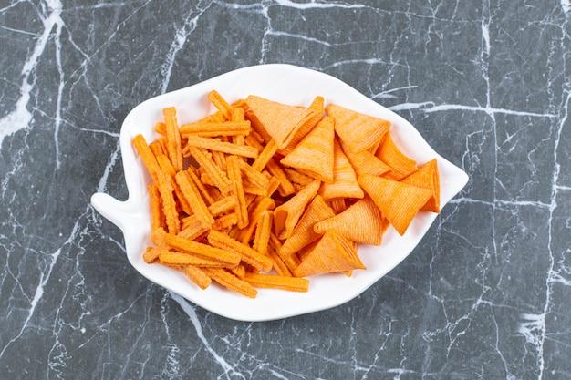 Pyszne chrupiące paluszki i trójkątne chipsy na talerzu w kształcie liścia.