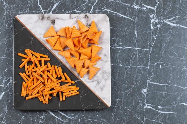 Pyszne chrupiące paluszki i trójkątne chipsy na talerzu.