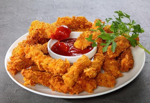 Pyszne chrupiące panierowane paski piersi kurczaka z sosem pomidorowym na białym talerzu
