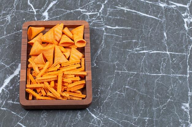 Pyszne chrupiące patyczki i trójkątne chipsy na drewnianym talerzu.