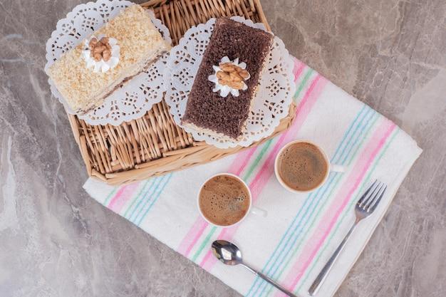 Pyszne ciasta i filiżanki kaw na obrusie.