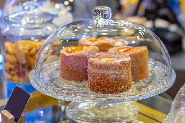 Pyszne ciasta w szklanym stojaku na ciasto na blacie kawiarni. deserowy bufet, przechowywanie
